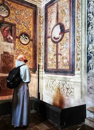 Un fraile observando los frescos de San Giovenale.