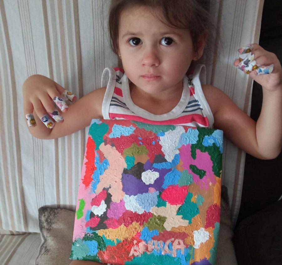 La niña posa con una de sus obras. PROPRONEWS