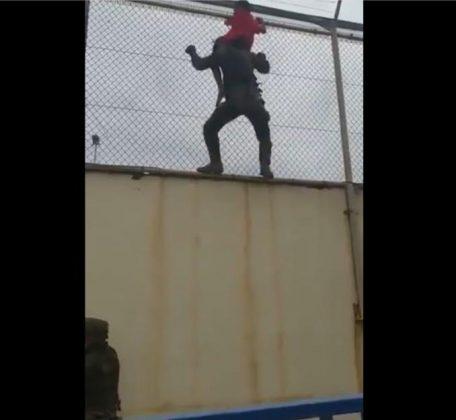 Un legionario rescata a la niña de lo alto de la valla, ante la atenta mirada de un compañero,abajo a la izquierda. RTVE