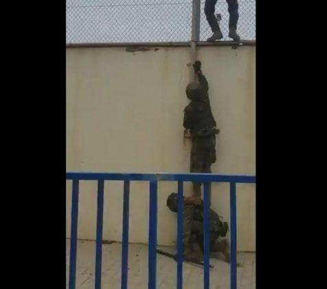 Dos legionarios se las ingenian para llegar a lo alto del muro, asegurar la estabilidad de su compañero y recoger a la pequeña. RTVE