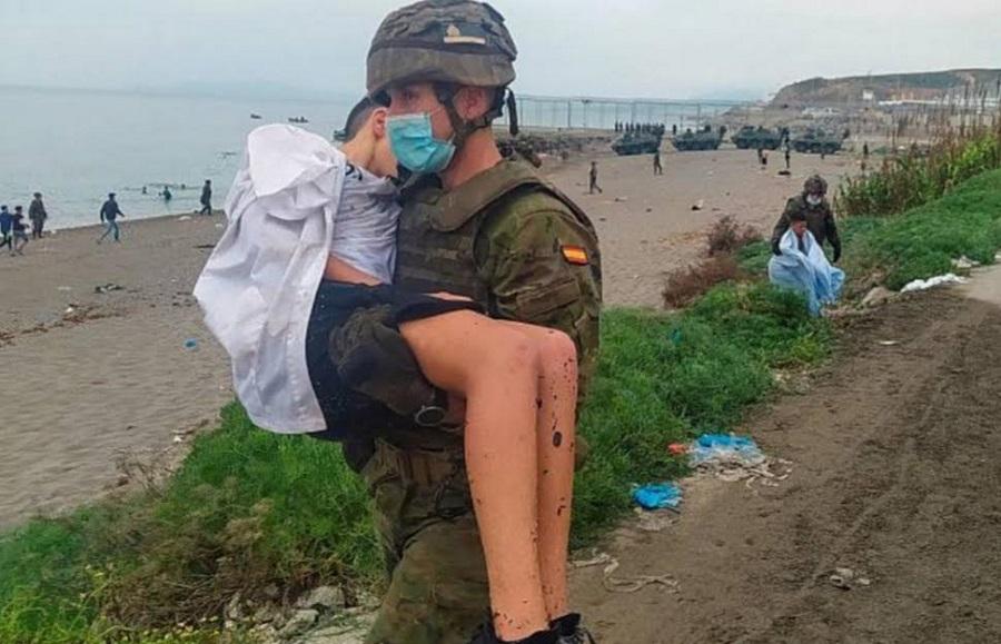 Un soldado del Ejército de Tierra lleva en brazos a un menor exhausto. RTVE