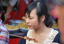 Una joven comiendo en un puesto de comida callejera en Pekín. J.M. PAGADOR